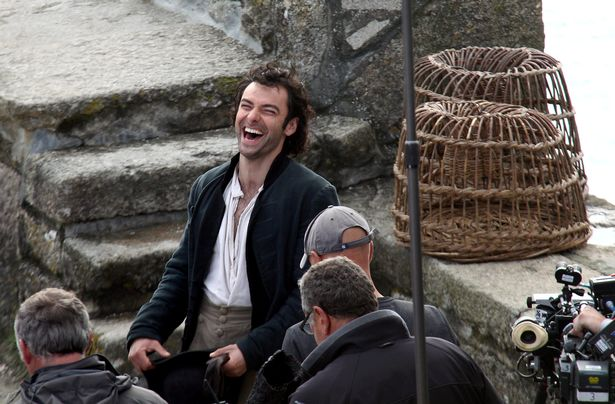 Aidan Turner shares a joke during a break from filming (Image: SWNS)